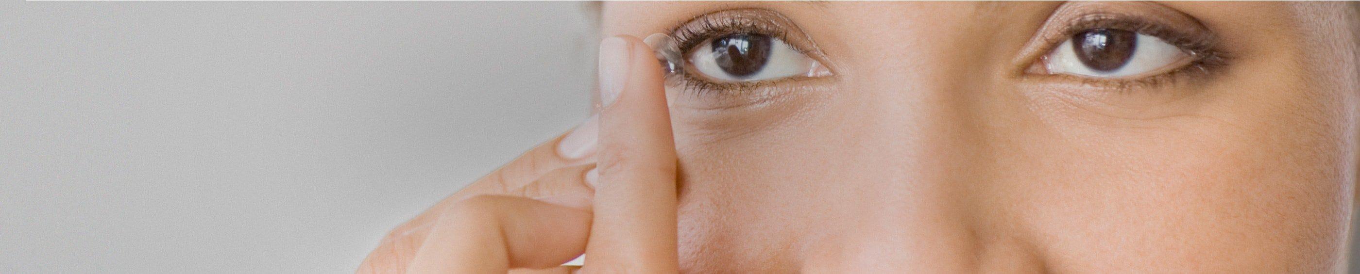 Junge Frau, die sich eine Kontaktlinse einsetzt