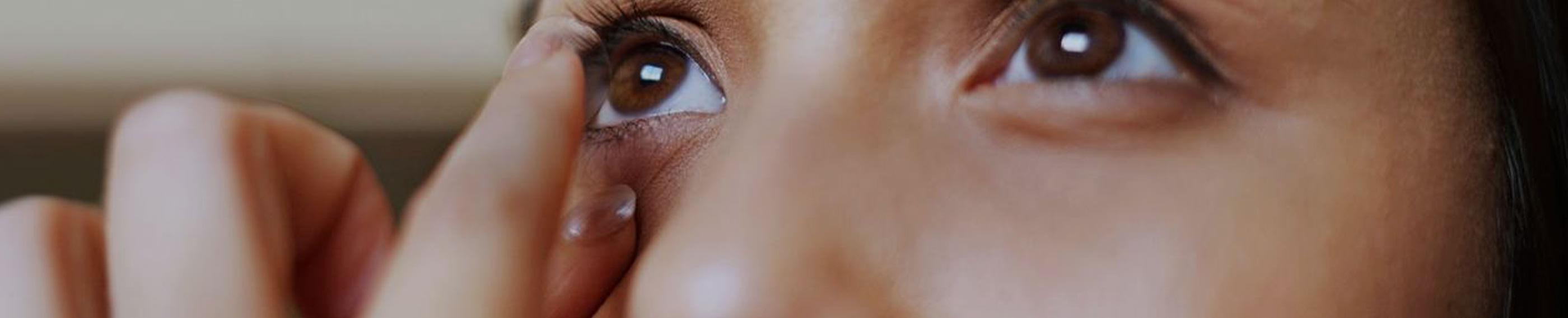 Nahaufnahme einer jungen Frau, die sich vor dem Spiegel ihre Kontaktlinsen einsetzt.