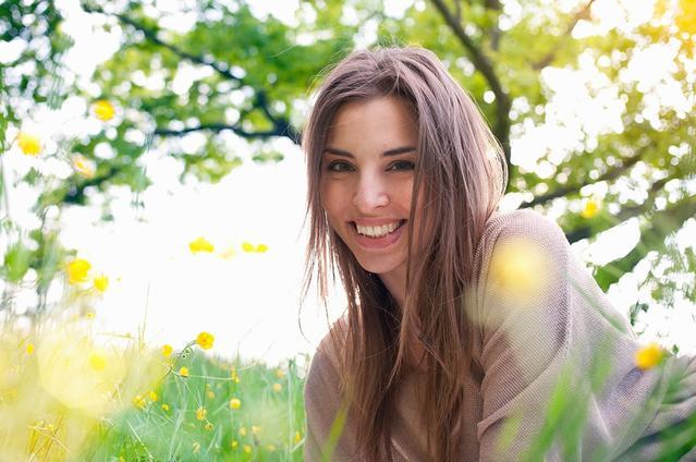 Junge lächelnde Frau, die bei Sonnenschein im Gras liegt.