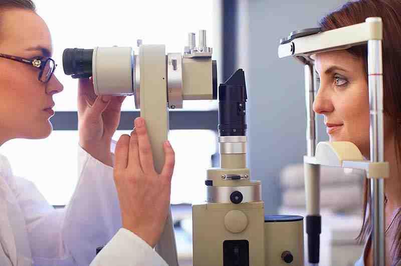 Seitenansicht einer jungen Frau bei der Augenuntersuchung durch einen Kontaktlinsenspezialisten.