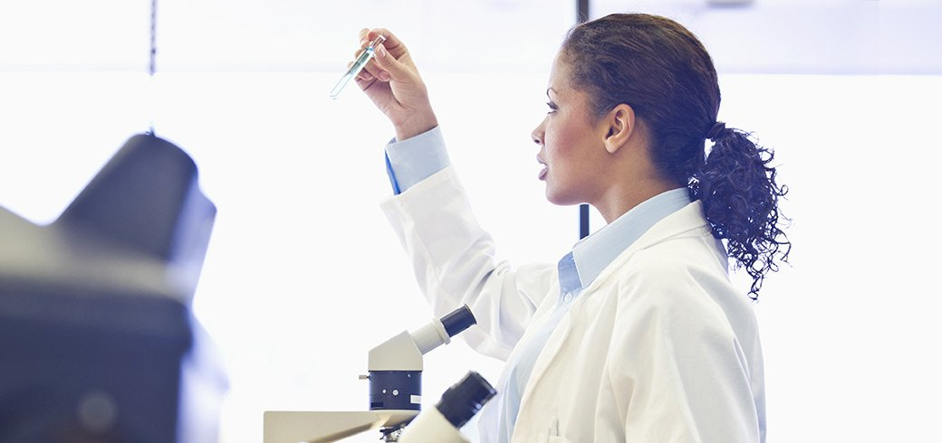 Ein Mediziner betrachtet ein Reagenzglas im Labor