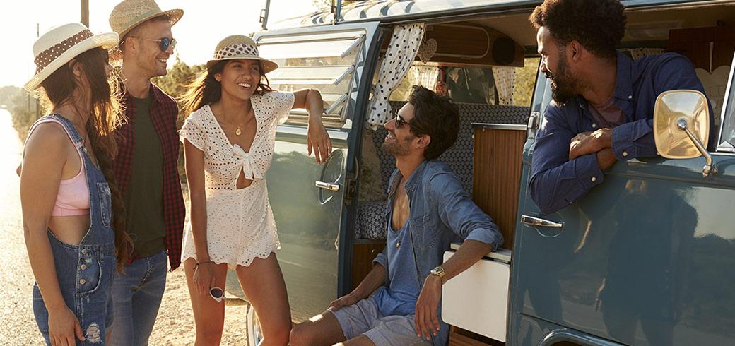 Eine Gruppe von Freunden unterhält sich mit anderen an deren Van in der Sonne.