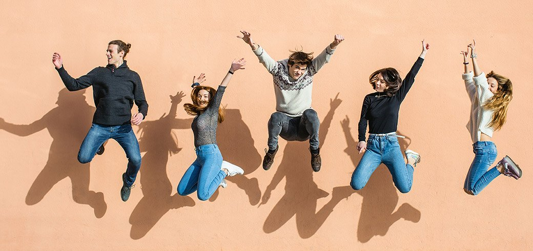 Eine Gruppe von Freunden, welche in die Luft sprint und lacht.