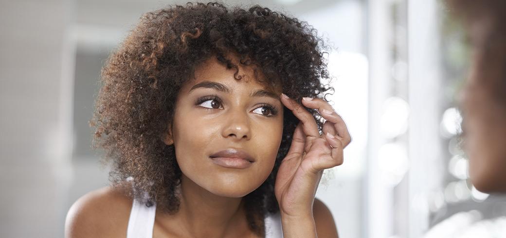 Junge Frau, die ihre Augen im Spiegel betrachtet