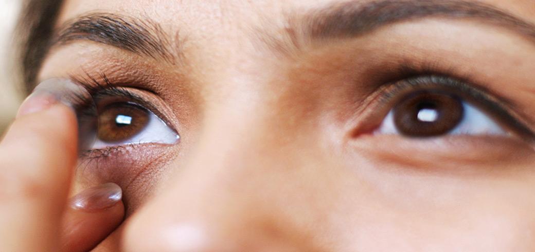 Nahaufnahme einer jungen Frau, die Kontaktlinsen aufsetzt.